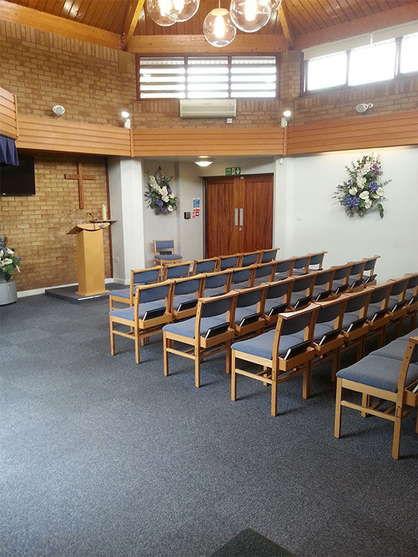 View inside one of the chapels, showing rows of seating and wall decorations